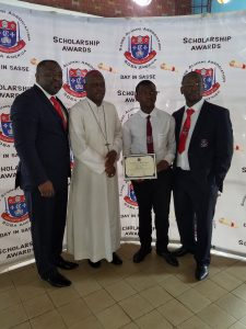 One of the laureates receiving his award from Bishop Bushu as President Itoe and Chairman Fote look on.